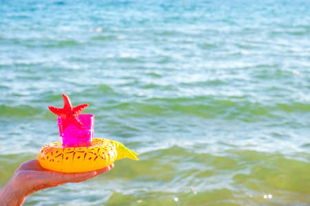 A pink plastic glass with soft drink and toy starfish in the hand of a mature man on the background of the sea. Healthy lifestyle and usefulness of the sea climate concept