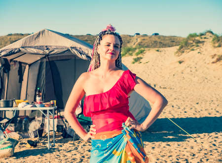 Beautiful caucasian woman with african braids enjoying the freedom in free camping at the beach and tent alternative people travel concept