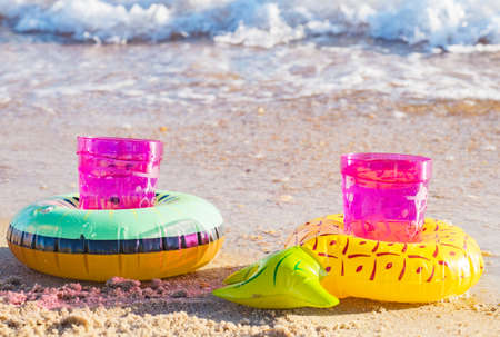 Two pink plastic glasses with a drink inserted into inflatable decorative coasters in the form of fruits on sand on the beach. Valentine's day concept
