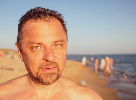 Portrait of middle aged man at beach looking at the camera.