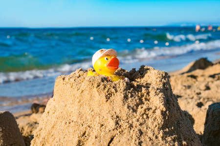 yellow rubber duck on top of a large number of sand against the sea, summer holiday concept Standard-Bild