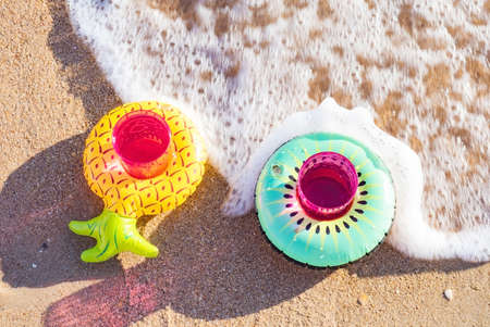 Two pink plastic glasses with a drink inserted into inflatable decorative coasters in the form of fruits on sand on the beach. Valentine's day concept. top view