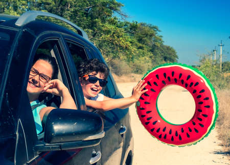 Family trip concept on the road to the sea: Portrait of two happy children swinging an inflatable ring at the camera, pouring their heads out of the car window Standard-Bild