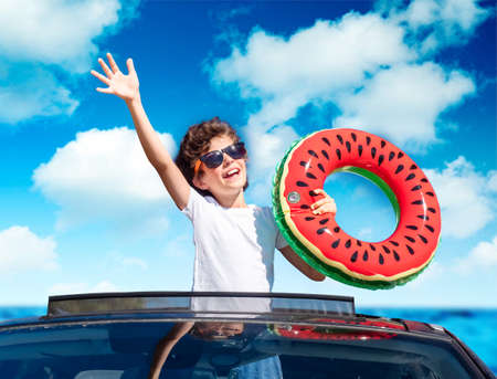 A little boy leaning out of the hatch of a car holding an inflatable ring is enjoying the journey and the trip to the sea. Happy child on the roof of the car raising his hands up