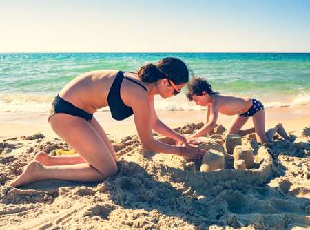 Brother and sister makes a sand castle on a tropical beach. Holidays, vacation, lifestyle concept.
