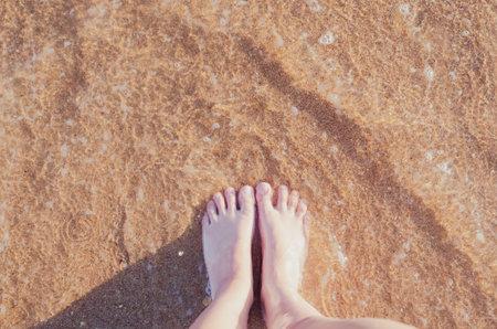 Relax on the ocean beach, female feet on the sea sand. Summer vacation concept