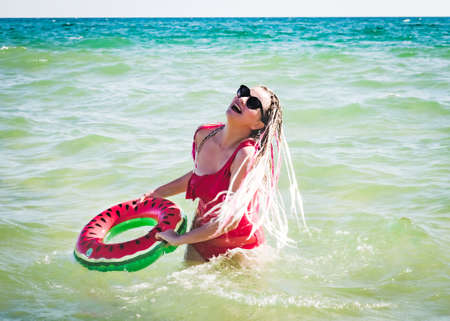 A cheerful middle-aged woman with a watermelon wedge swimming circle swimming in a sea. The concept of leisure and entertainment Standard-Bild