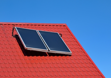Solar panel on a red roof on blue sky photo