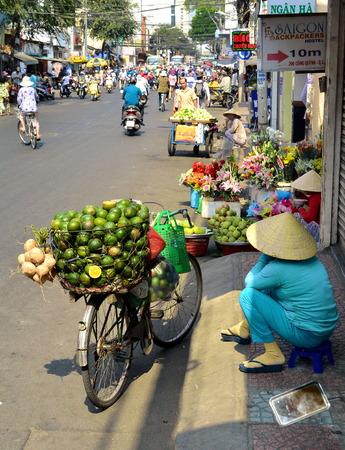 street vendor: SAIGION, VIETNAM March 06: Woman street vendor selling large green fruit in Vietnam