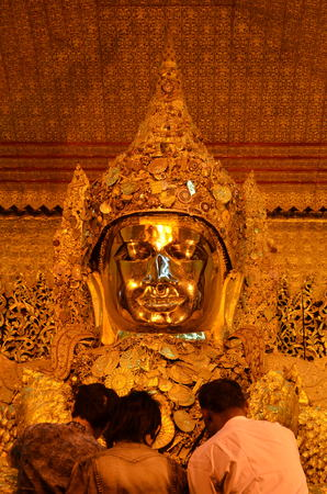 buddhism prayer belief: Mandalay - March 14 2015: The Myanmar people venerated Buddha statue with the golden paper at Mahamuni Buddha temple