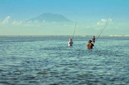nusa: Traditional Balinese fishermen standing in shallow water at low tide on the beach at Nusa Dua Stock Photo