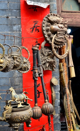 PINGYAO, CHINA - May 7, 2017 - Old metal souvenirs and decoration from China on market in Pingyao