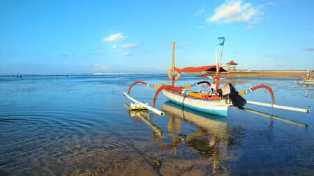 Boat on beach in sunset time at low tide Indonesia