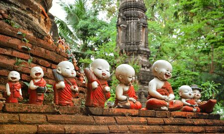 Sculpture of little monks with bowls at the buddhists temple in Ayutthaya
