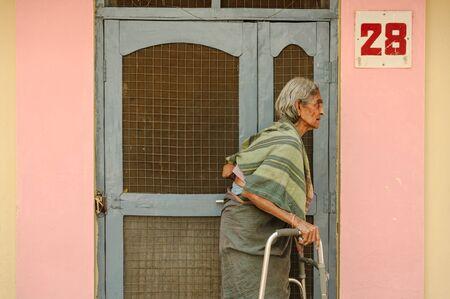 old indian woman stands with go-carts near the entrance to residental barrack. 8 february 2018 Sai Baba Ashram Puttaparthi Редакционное