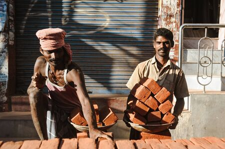 two indian workers in outdoors with plates ful of bricks, 23 february 2018 Madurai, India Editorial
