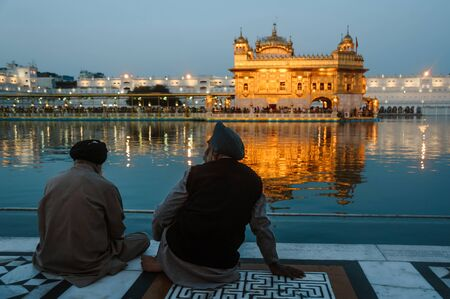 Two indian sikhs mans sits near the water of golden temple at night. 24 february 2018 Amritsar, India.