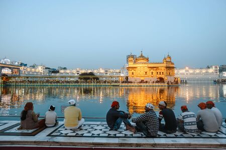 Group of indian sikhs mans sits near the water of golden temple at night. 24 february 2018 Amritsar, India. Editorial