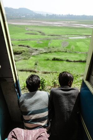 27 february 2018 Amritsar, India. two indian boys in train doors and lookint ant beautiful green landscape.