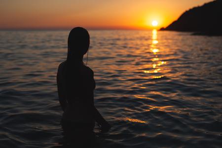 wet woman sunset silhouette in ocean water. Sea bathing at dawn
