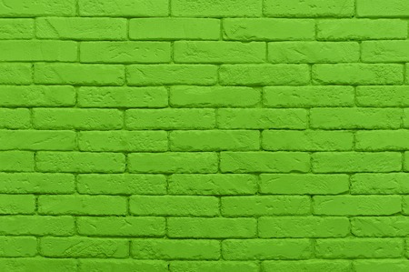 green brick wall painted at saturated lime colour. closeup texture background