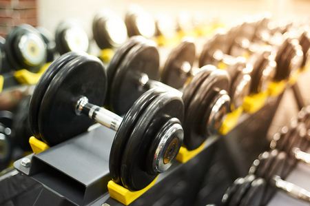 dumbbells row in a gym. sport sunny background. closeup. copy space