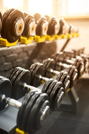 dumbbells row in a gym. sport sunny background. closeup vertical. copy space.