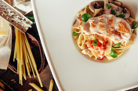 fettuccine pasta with chicken breast and mushroom composition at dark wood background