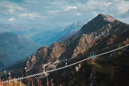 Beautiful mountain landscape with blue coudy sky. Suspension extreme bridge at Rosa Peak top. Rosa khutor resort