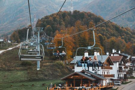 People seats at cableway elevator. Cable car road at Rosa Khutor Resort - Russia, Sochi, 10.10.2018