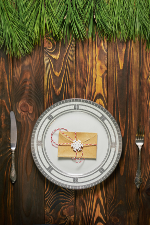 christmas table setting at brown wooden background with white plate, silver cutlery and paper envelope. xmas concept. vertical top view Stock Photo