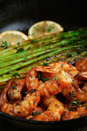 fried langoustines with asparagus decorated with lemon slices. roasted king prawns tiger shrimps with green garnish. home cooking. vertical
