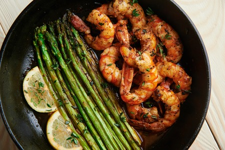 fried langoustines with asparagus decorated with lemon slices. roasted king prawns tiger shrimps with green garnish. home cooking.