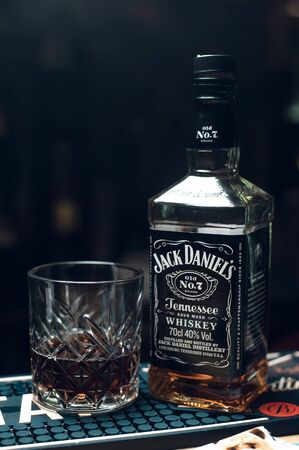 26.01.2019. Russia, Sevastopol. jack daniels bottle with half ful glass at bar counter in dark, vertical. copy space. Editorial