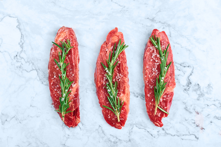 raw marbled beef steaks with green rosemary branch and sea salt at white marble background. Copy space Zdjęcie Seryjne