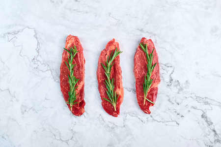 raw marbled beef steaks with green rosemary branch at white marble background. copy space
