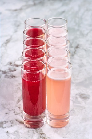 两排酒精鸡尾酒珊瑚色和红色的饮料。垂直