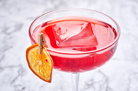 red cocktail with big piece of ice decorated with dried slice of orange. Copy space. Close up