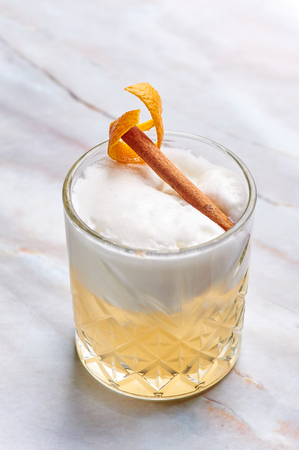 whisky sour alcohol cocktail with egg white, orange cedar and cinnamon. vertical
