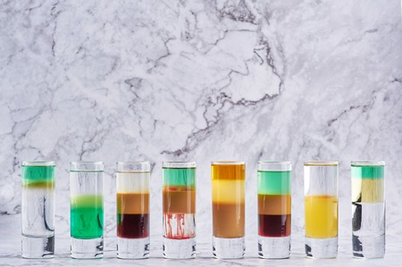 row of eight different alcohol shot cocktails at marble backdrop. Copy space