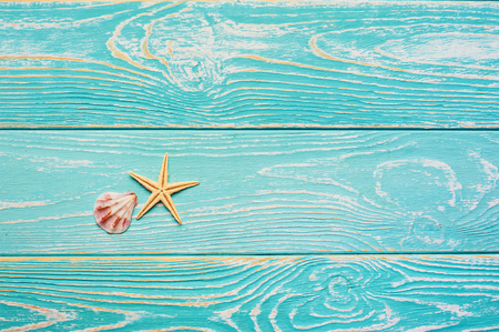 blue wooden background with starfish and shell. Summer beach minimal concept with free space for text. sea vacation backdrop