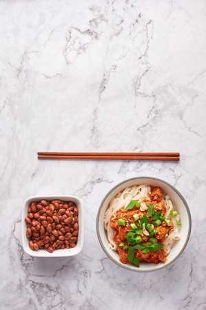 shan noodles with peanuts and chopsticks at white marble tabletop. burmese cuisine traditional dish. myanmar food. rice noodles with pork in tomatos Stock Photo