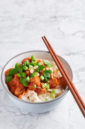 shan noodles with chopsticks at white marble tabletop. burmese cuisine traditional dish. myanmar food. rice noodles with pork in tomatos. asian dish Stock Photo