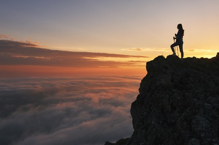 silhouette of hiker woman with trekking poles stands at rock and looks at aerial view in the mountains above the clouds. Mountains sunset landscape with tourist silhouette in orange sun light.