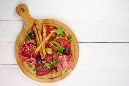 meat platter at white wooden table top with grissini, prosciutto, salami, sausage, and olives. top view. Copy space. Free space for your text