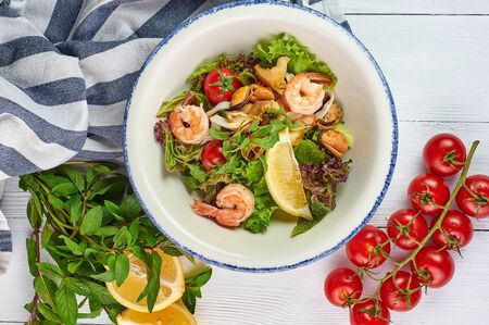 seafood salad decorated with cherry tomatoes mint and lemon at white wooden table top. Salad with prawns, mussels andsquid.