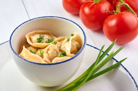 dumplings with parsley and onion at white wooden table top. Pelmeni - traditional russian cuisine dish dough with minced meat inside. decorated with tomatoes Stock fotó