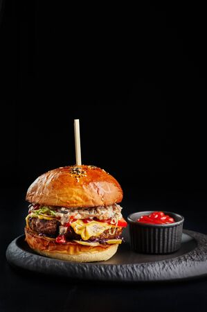 perfect burger with big beef cutlet, cheese, tomatoes, mushroom sauce and ketchup at black background with copy space.