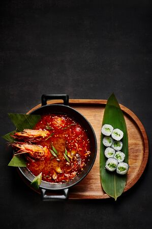 Tom yum soup with maki roll at black
