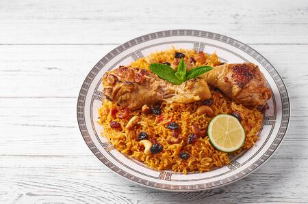 Chicken Kabsa or Chicken biryani at white wooden background. Kabsa is traditional saudi arabian cuisine dish. Kabsa cooks with basmati rice, chicken, spices, tomatoes, nuts and raisins Copy space 版權商用圖片